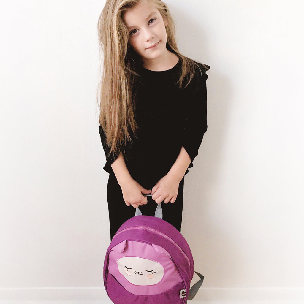 Little girl holding a purple Kawaii Pac mini backpack by Milkdot.