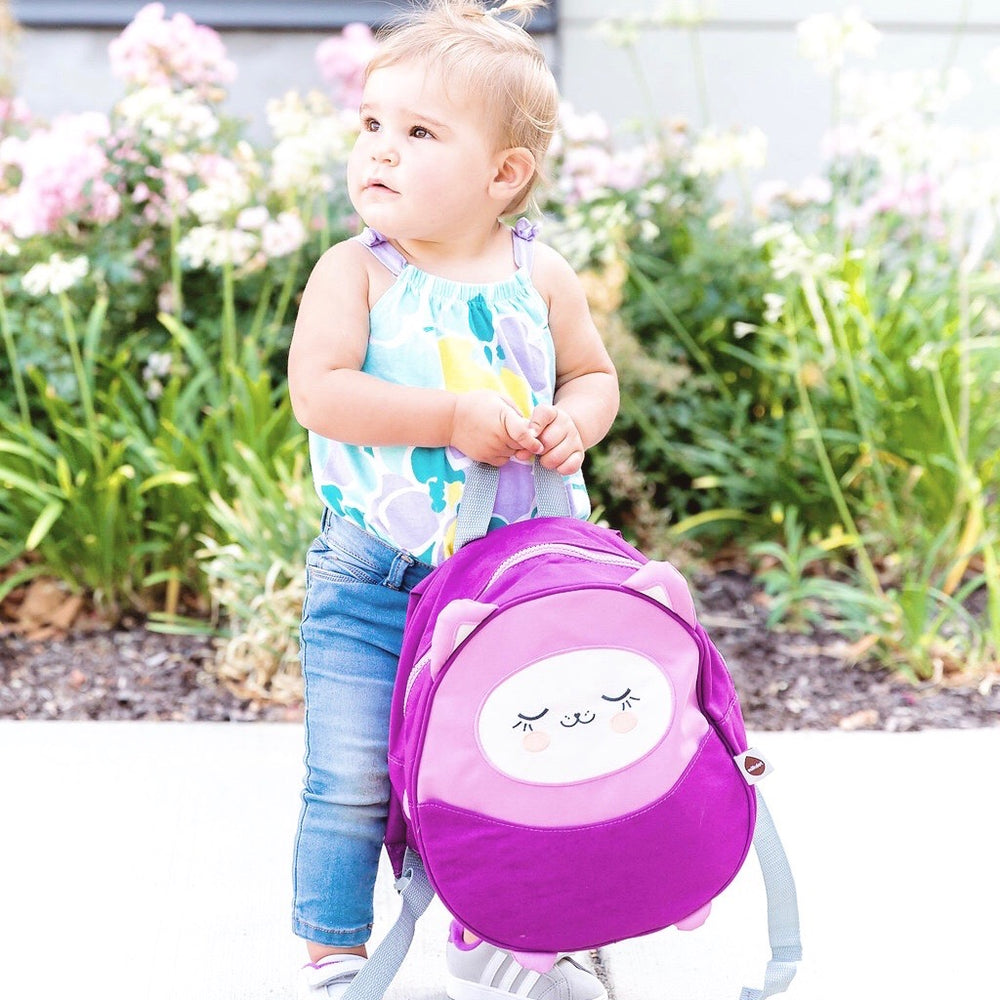 Cute toddler holding a Milkdot Lola mini backpack in front of a flower garden