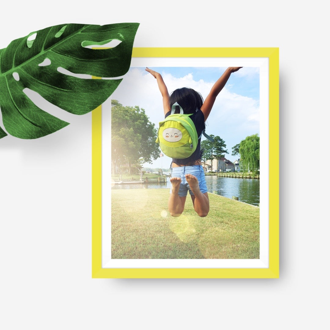 Yellow frame of a girl jumping for joy outside with her Milkdot green mini backpack
