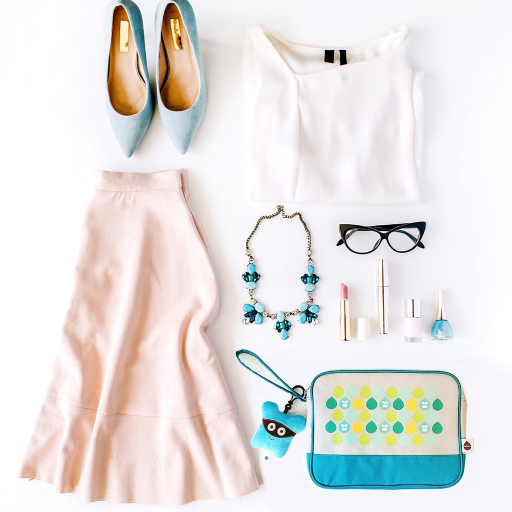 Milkdot blue toiletry travel bag in a flatlay with our Koaro plush key ring, dressy outfit, makeup, necklace and glasses