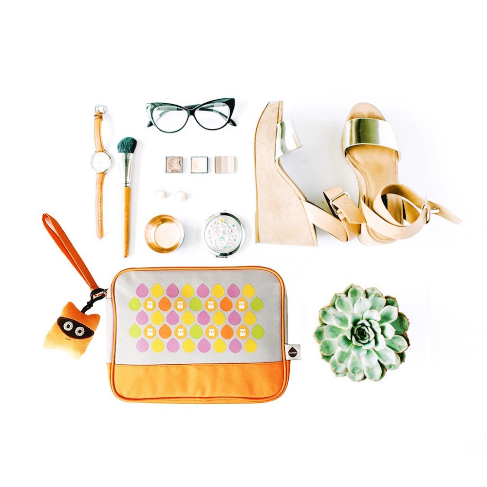 Orange Milkdot toiletry travel bag in a flat lay with our Kitiro plush key ring, watch, glasses, makeup and summer wedge sandles