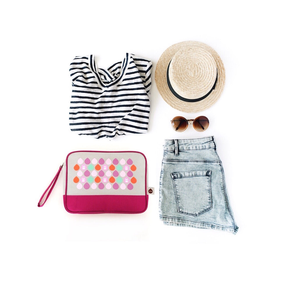 Flat lay for summer travels with a Milkdot travel toiletry bag, striped t-shirt, jean shorts, sunglasses and straw hat