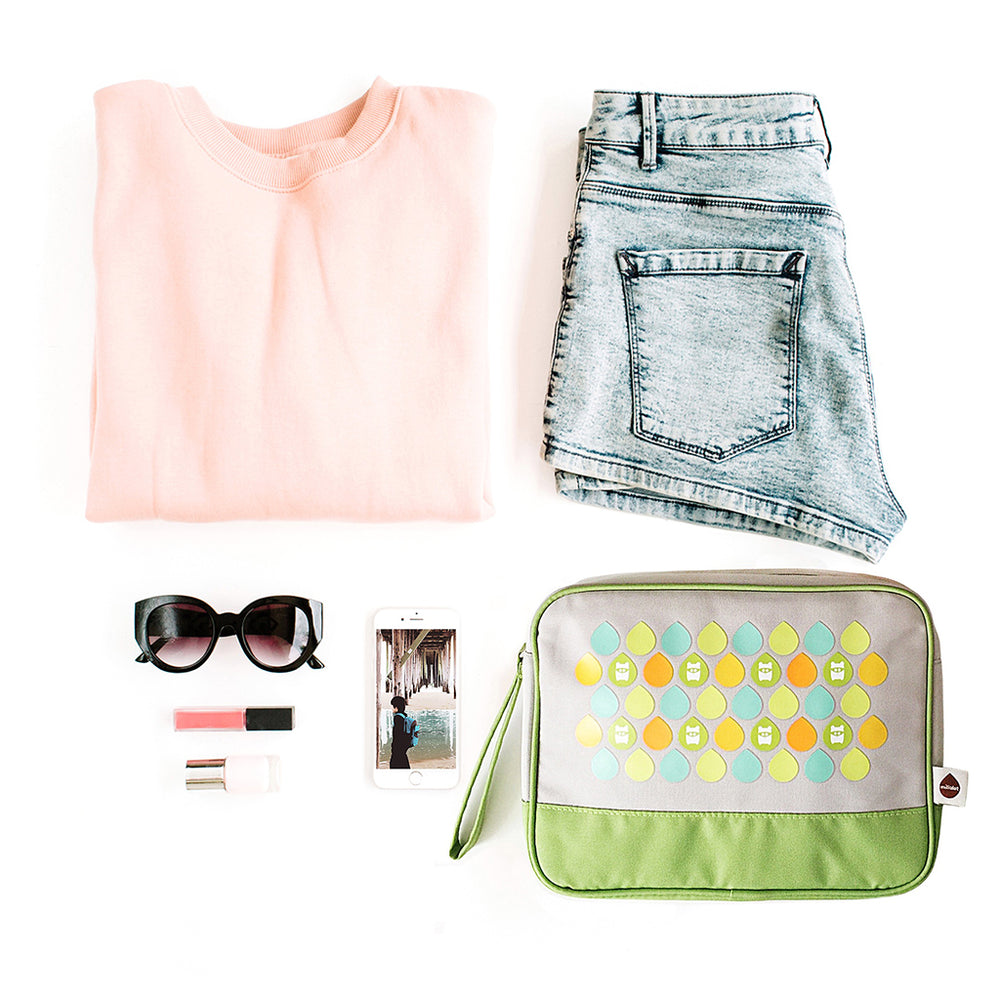 flat lay of pink shirt, jean shorts, sunglasses, phone and Milkdot toiletry bag in lime dots