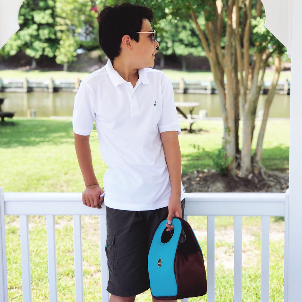 boy in a white shirt holding a blue raspberry Milkdot lunch bag