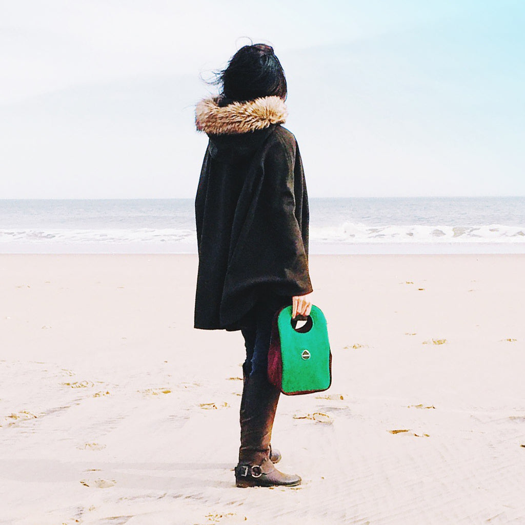 Woman on the beach holding a green Stoh Lunch Tote by Milkdot.