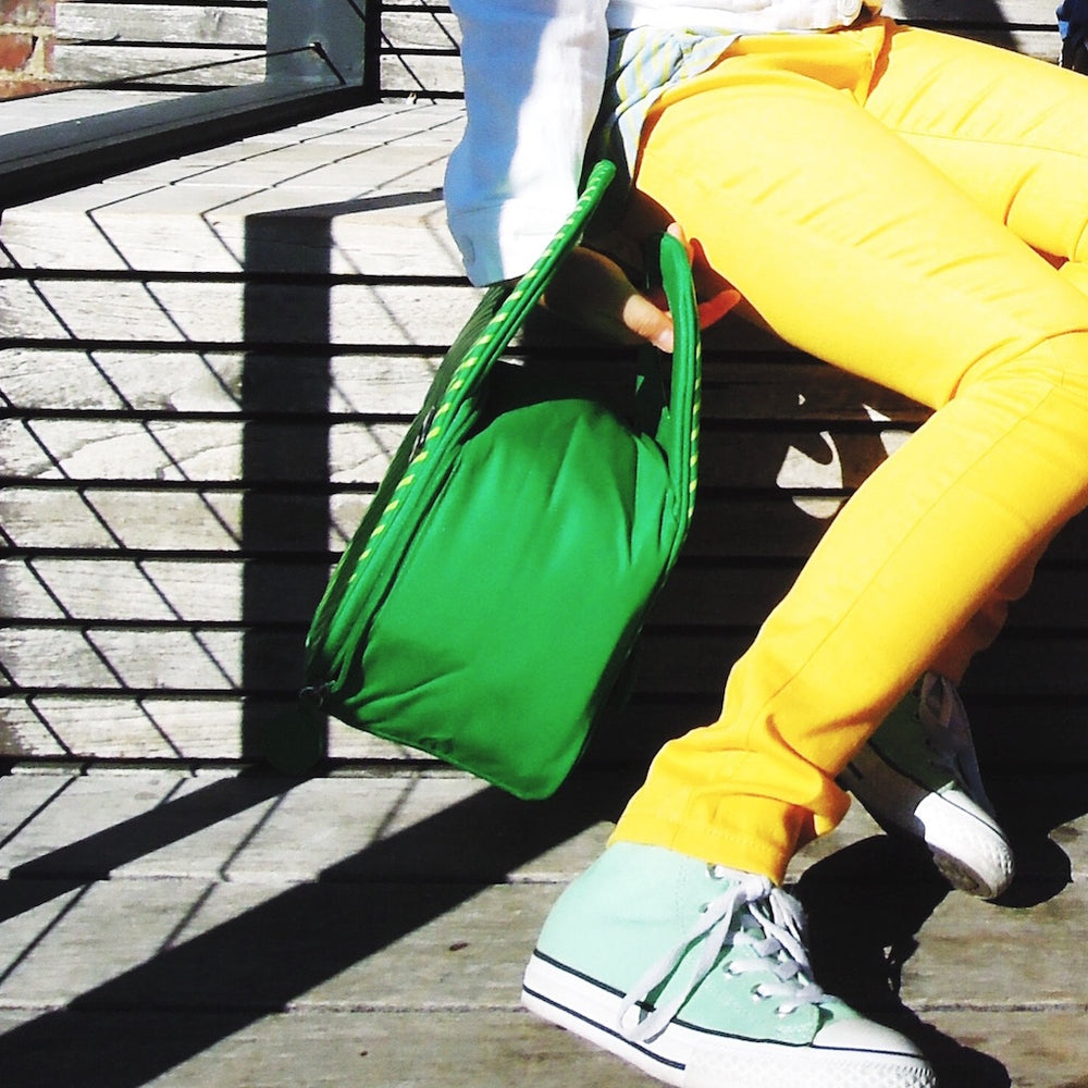 Close up photo of girl's legs wearing bright yellow jeans and holding a green Milkdot lunch bag