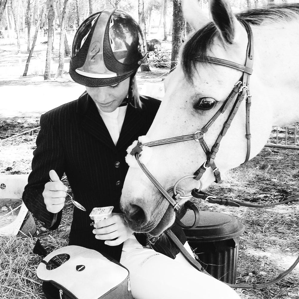 Black and white photo of a girl and her horse eating lunch with a Milkdot lunch bag