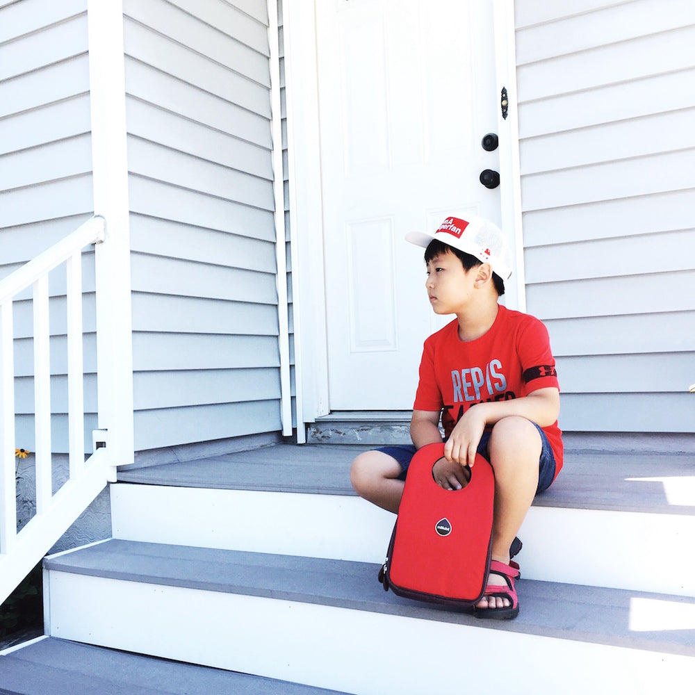 Little boy with a red shirt sitting on a white doorstep with a red Milkdot lunch bag