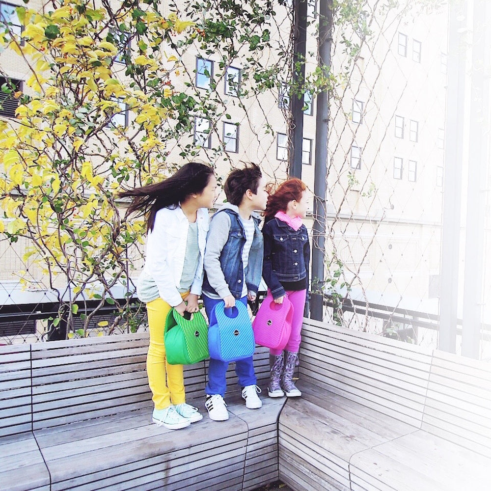 Three kids standing on a bench, each holding a Milkdot stripe lunch bag