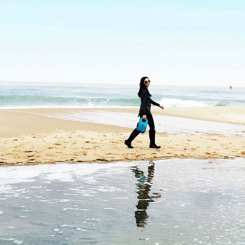 Woman walking on the beach carrying a blue Milkdot lunch box.