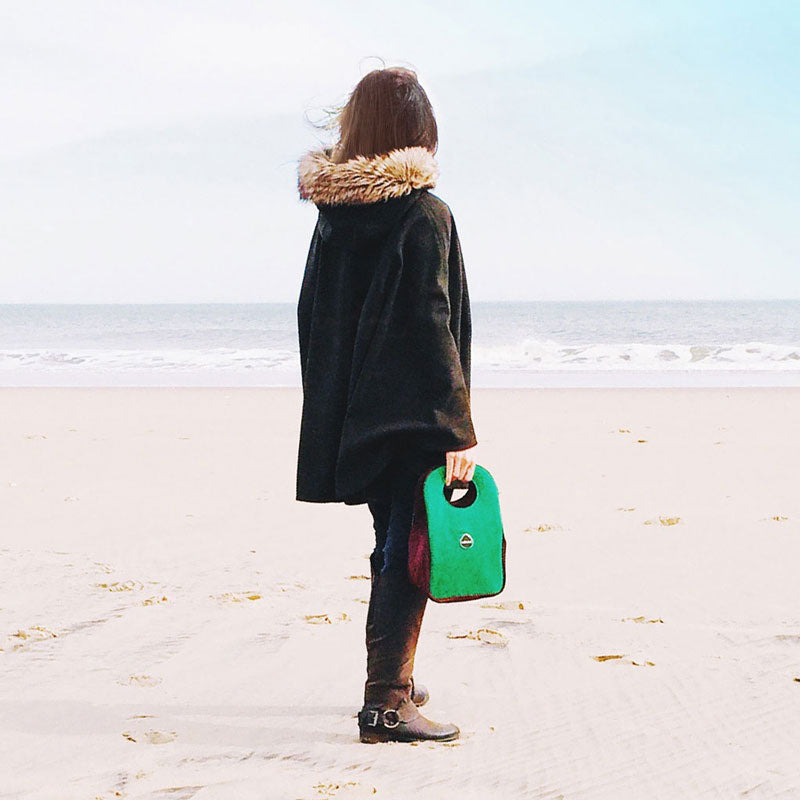 Woman on the beach holding a green Milkdot lunch box.