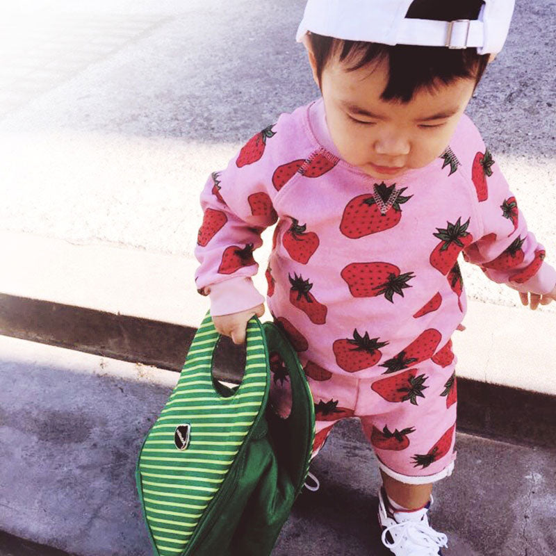 Cute toddler in pink holding a Milkdot green stripe lunch box.