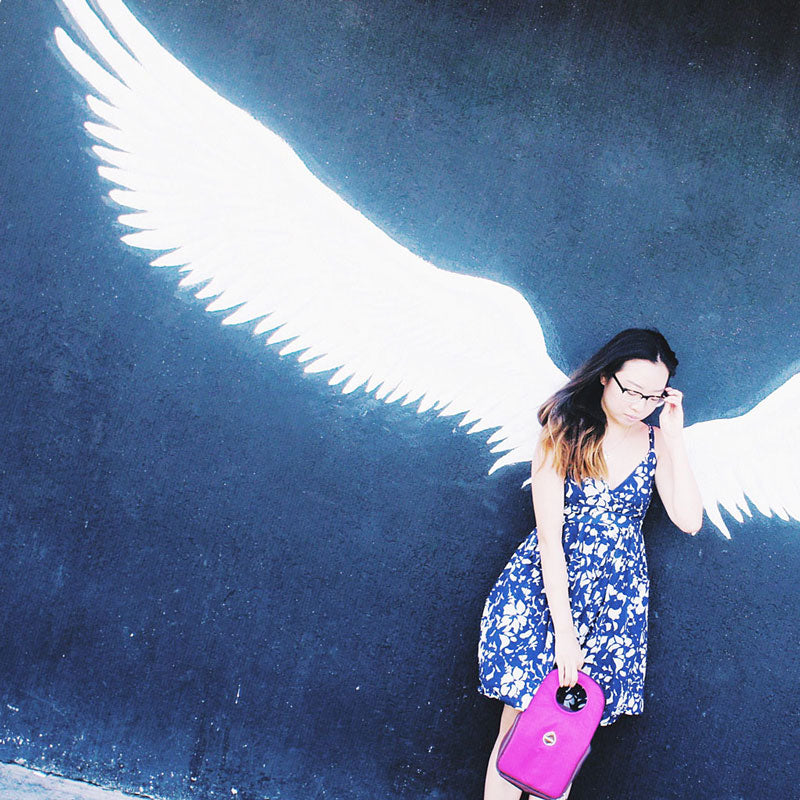 Woman holding a purple Milkdot lunch box in front of a wall painted with white wings.
