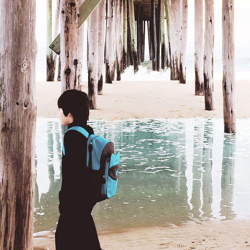 Boy wearing a blue Milkdot backpack, walking under a boardwalk.