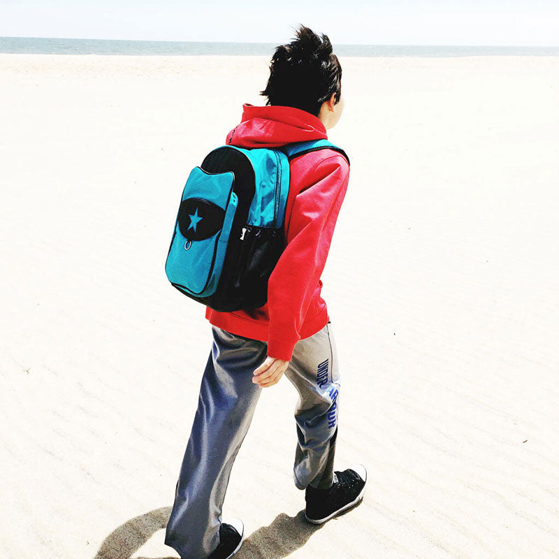 Boy on a beach wearing a blue Milkdot backpack and a red sweatshirt.