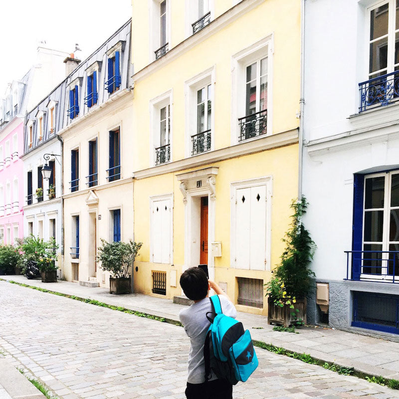 Boy wearing a blue Milkdot backpack taking a photo of pastel-colored buildings.