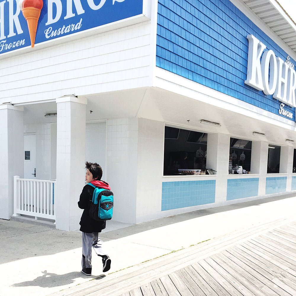 Boy on the boardwalk next to an ice cream shop wearing our blue raspberry Top Kat backpack