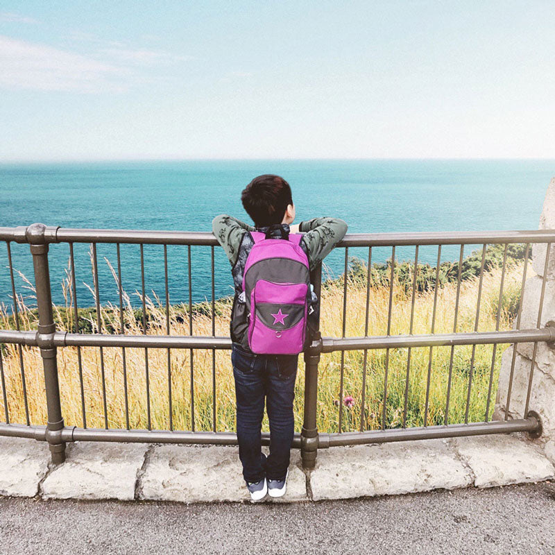 Boy looking at the ocean and wearing a purple Milkdot backpack.