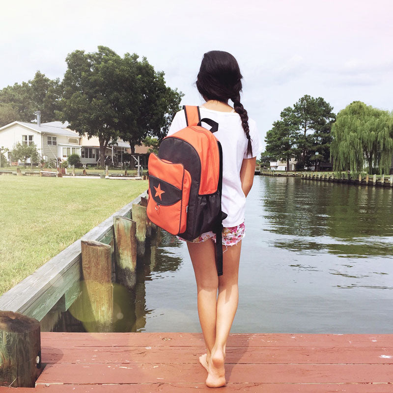 Girl facing the water wearing an orange Milkdot backpack.