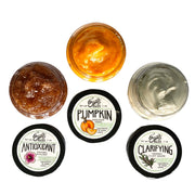 three swatches and 1oz jar lids of an antioxidant mask, enzyme peel and clay mask