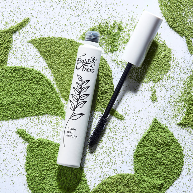 Matcha mascara tube and mascara brush with green and white leafy background