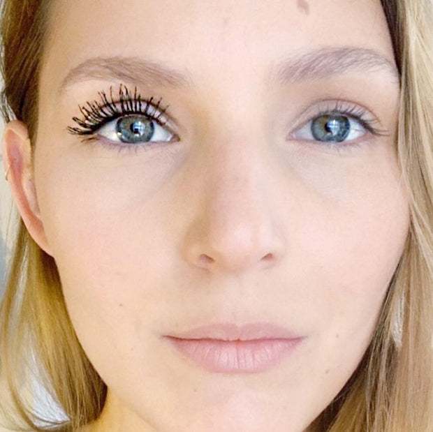 Woman's face with matcha mascara on eyelashes on one side of her face