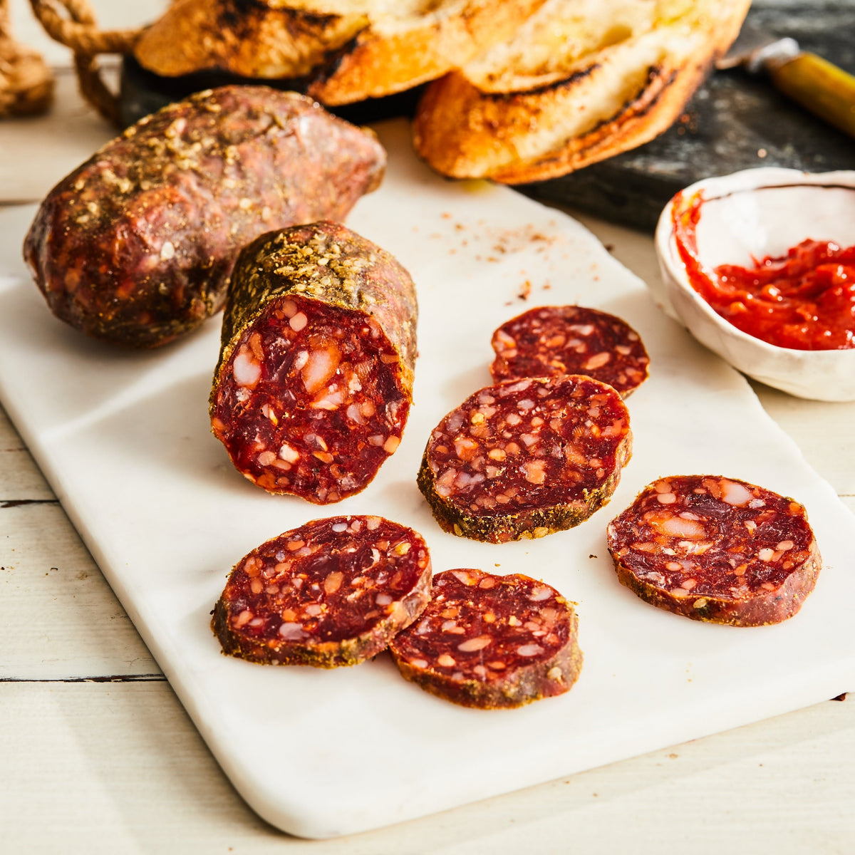 Image of Lamb Harissa Salami (no pork). 1 link, 3oz. a lamb salami with harissa (a spicy, aromatic chili paste), za'atar (a Middle Eastern blend of savory dried herbs), and preserved lemon