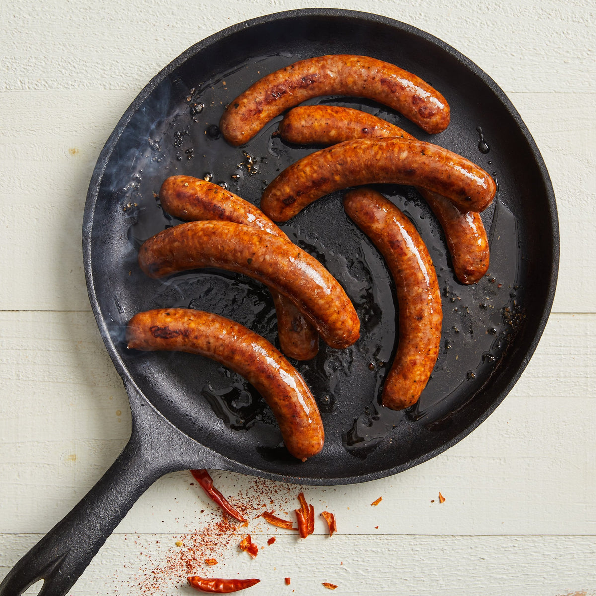 Image of Lamb Merguez (No Pork). 6-7 links, about 1 lb. an cooked take on the red, spicy sausage popular in Rance, North Africa and the Middle East featuring Pure Bred lamb and a variety of herbs and spices