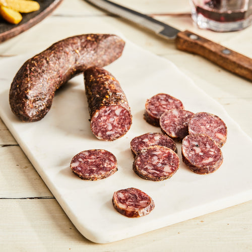 Image of Wagyu Beef au Poivre Salami. 1 link, 3 oz. a French-style salami made with Ohio-raised Wagyu beef, caramelized onion, Dijon and whole grain mustard, black pepper, green peppercorns, and brandy