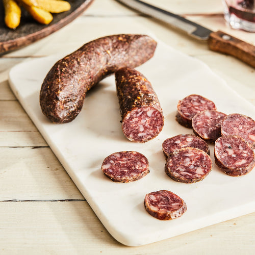 Image of Saucisson Sec with Herbs de Provence. 1 link, 3 oz. a traditional French pork salami with black pepper, pink pepper, garlic, and herbs de Provence