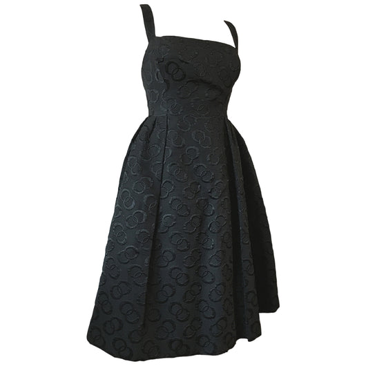 Sultry black late 1950s cocktail dress with interconnecting rings pattern