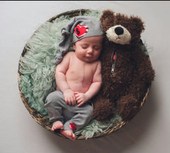 Little Heart Warrior and a Mended Heart Bummer Bear cozy in a basket together.