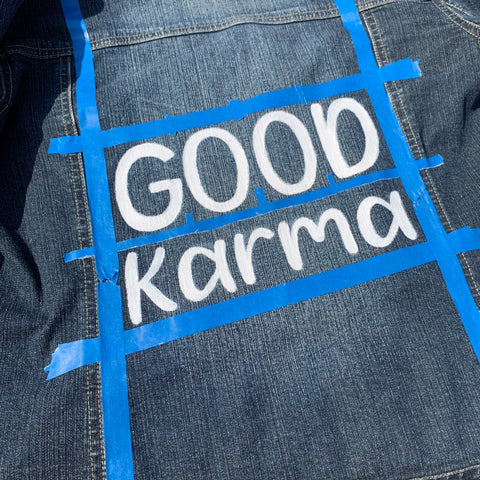 Good Karma painted on a denim jacket in white