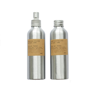 Two silver canisters with kraft labels, one with a metal spray nozzlw