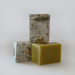 Three bars of soap. One yellow soap is unwrapped and two others have wrappers with images of oat plants
