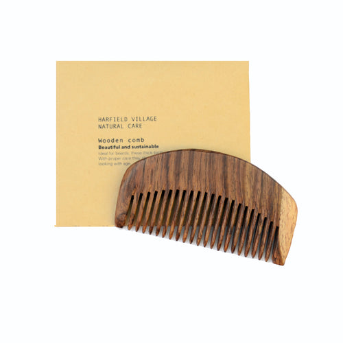 A wooden comb sits on top of a beige envelope