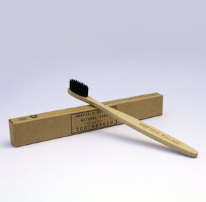 A natural coloured bamboo toothbrush with black bristles resting on a kraft cardboard box