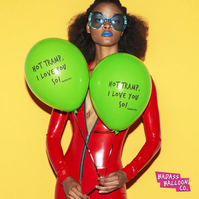 Shapely curly girl in sexy red jumpsuit holding green balloons that read Hot Tramp, I Love You So standing isolated on bright background. Sassy balloons by Badass Balloon Co.