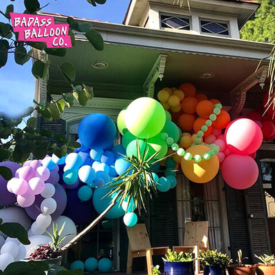 House decorated with a rainbow balloon garland. Balloons by Badass Balloon Co.