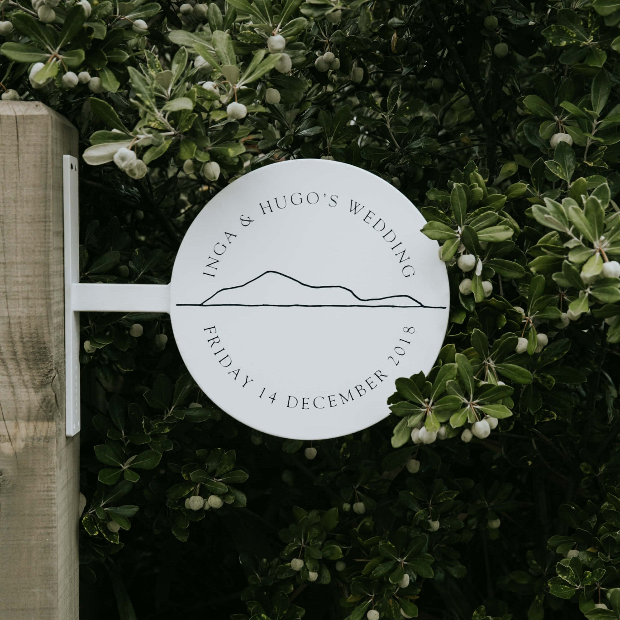 A white metal round sign displaying a wedding welcome sign