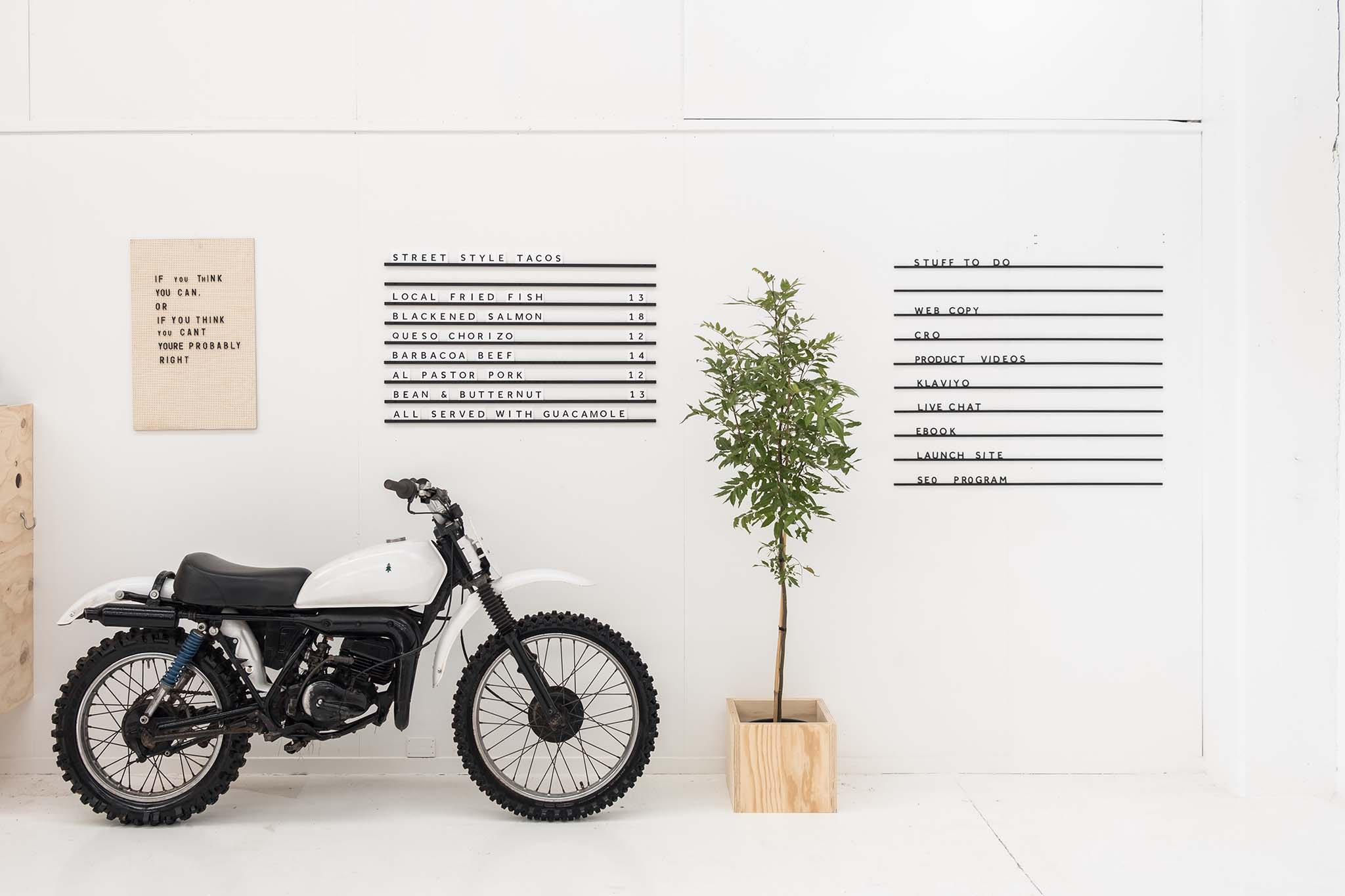 cafe menu board on white wall with motorbike next to it minimalistic office interior design