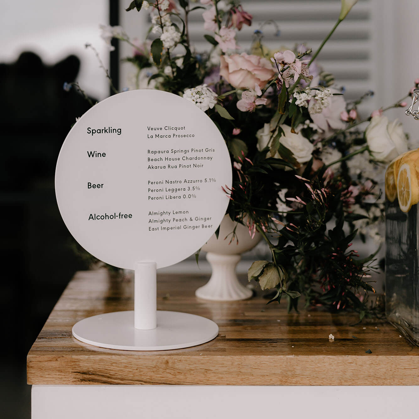 A small round circle sign on top of a counter displaying a drinks menu at a wedding