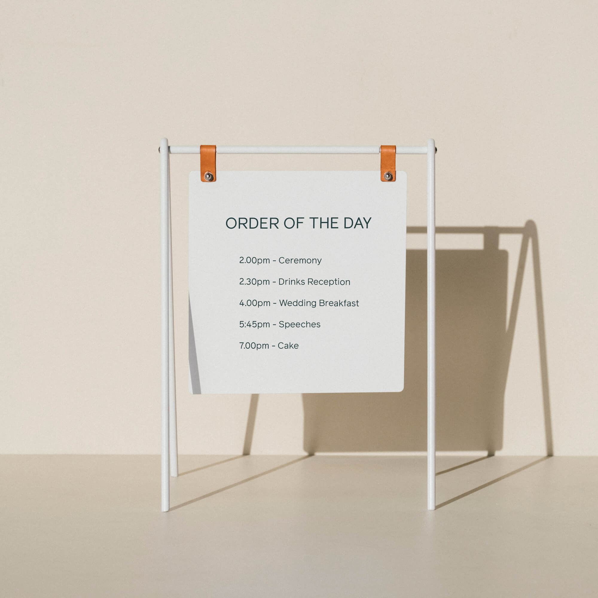 A miniature white A-frame sign displaying an order of the day for a wedding