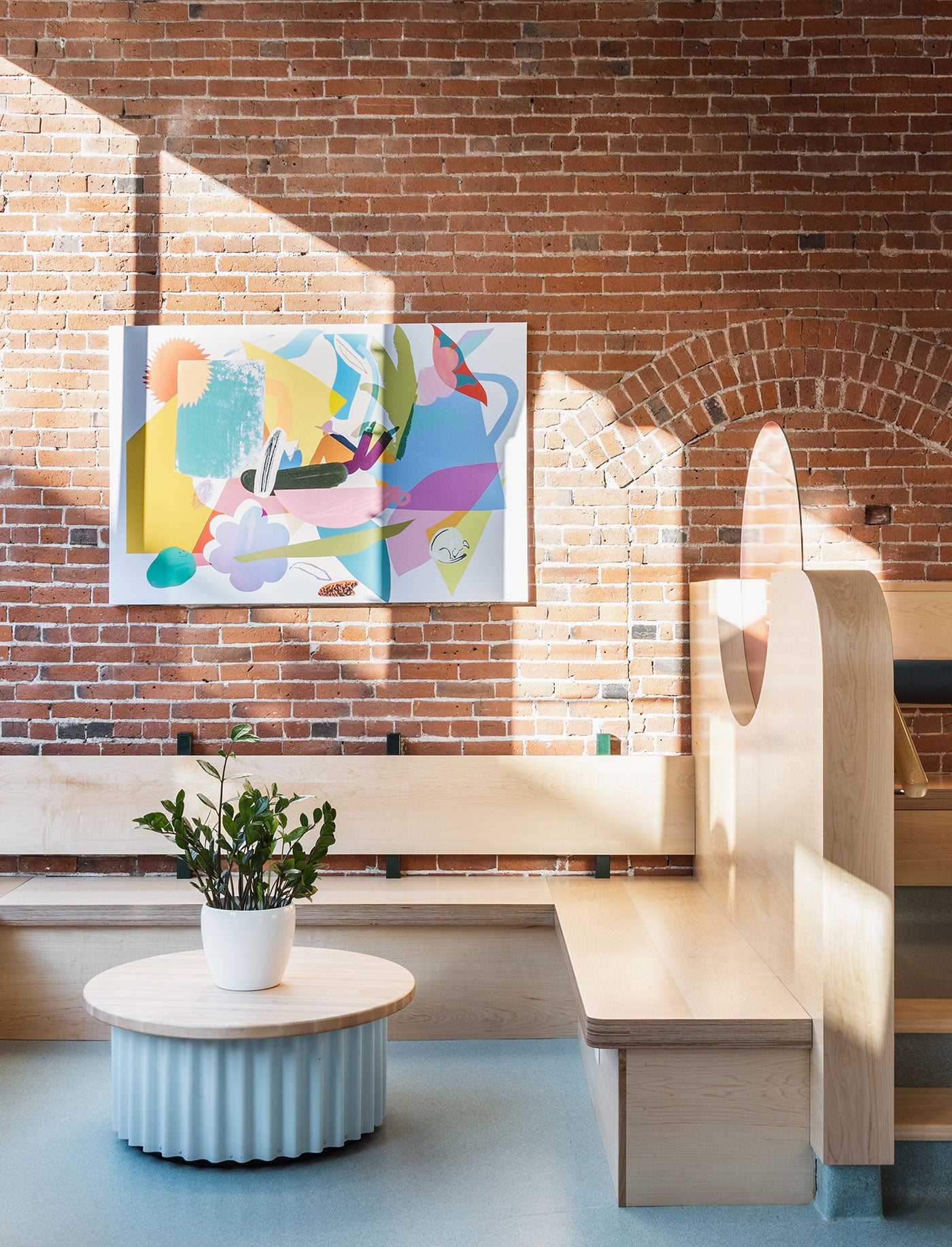 Bright modern cafe interior design featuring abstract art on brick wall