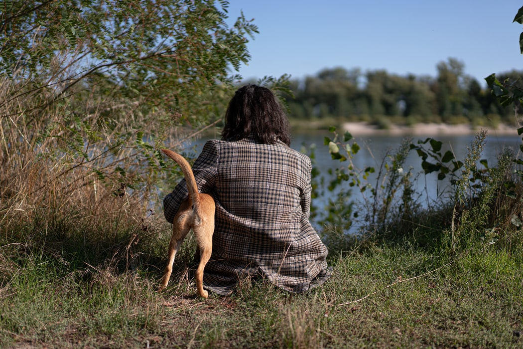 woman and dog sitting at lake