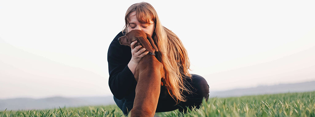woman with dog in field