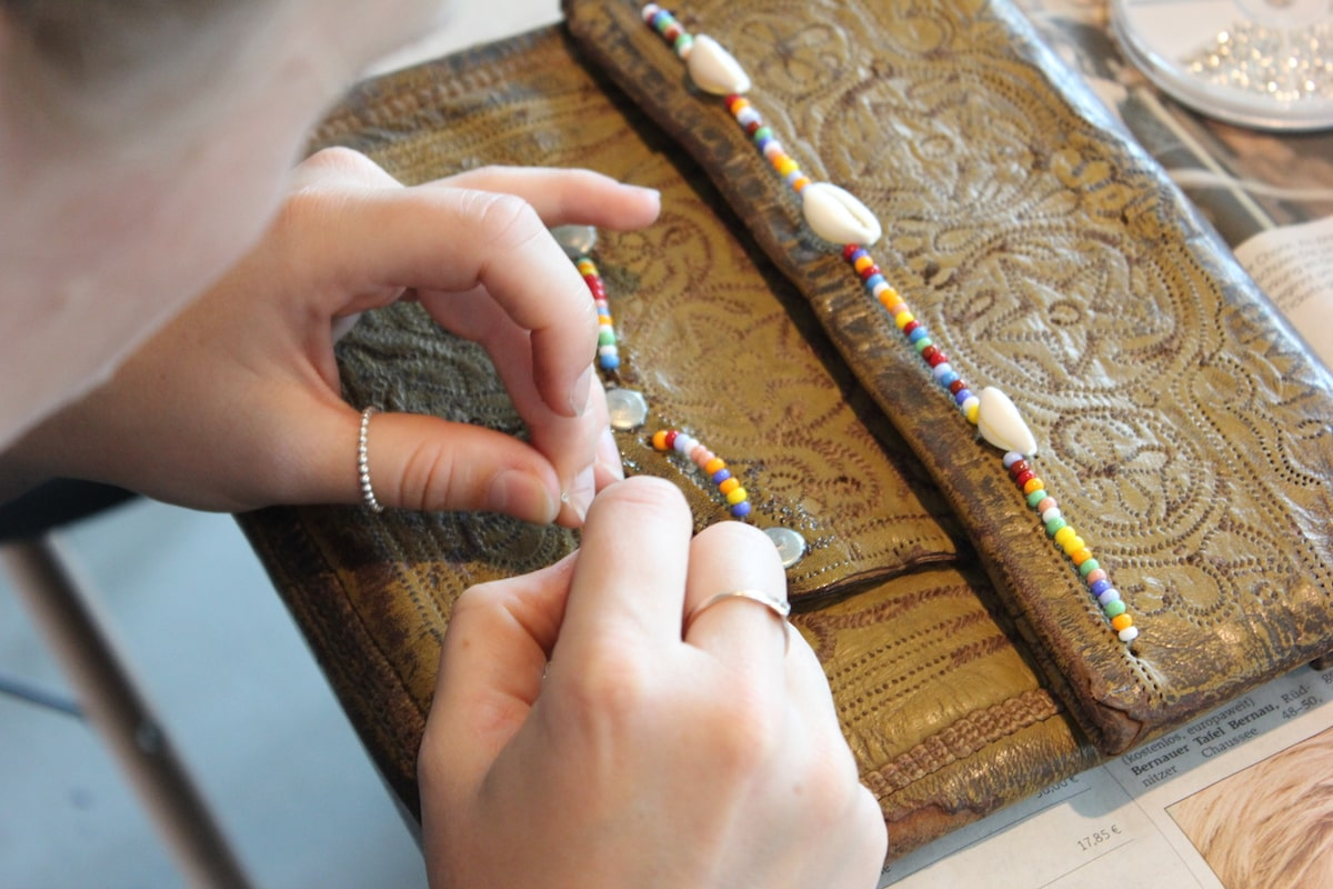 close up of someone customizing a vintage berber bag