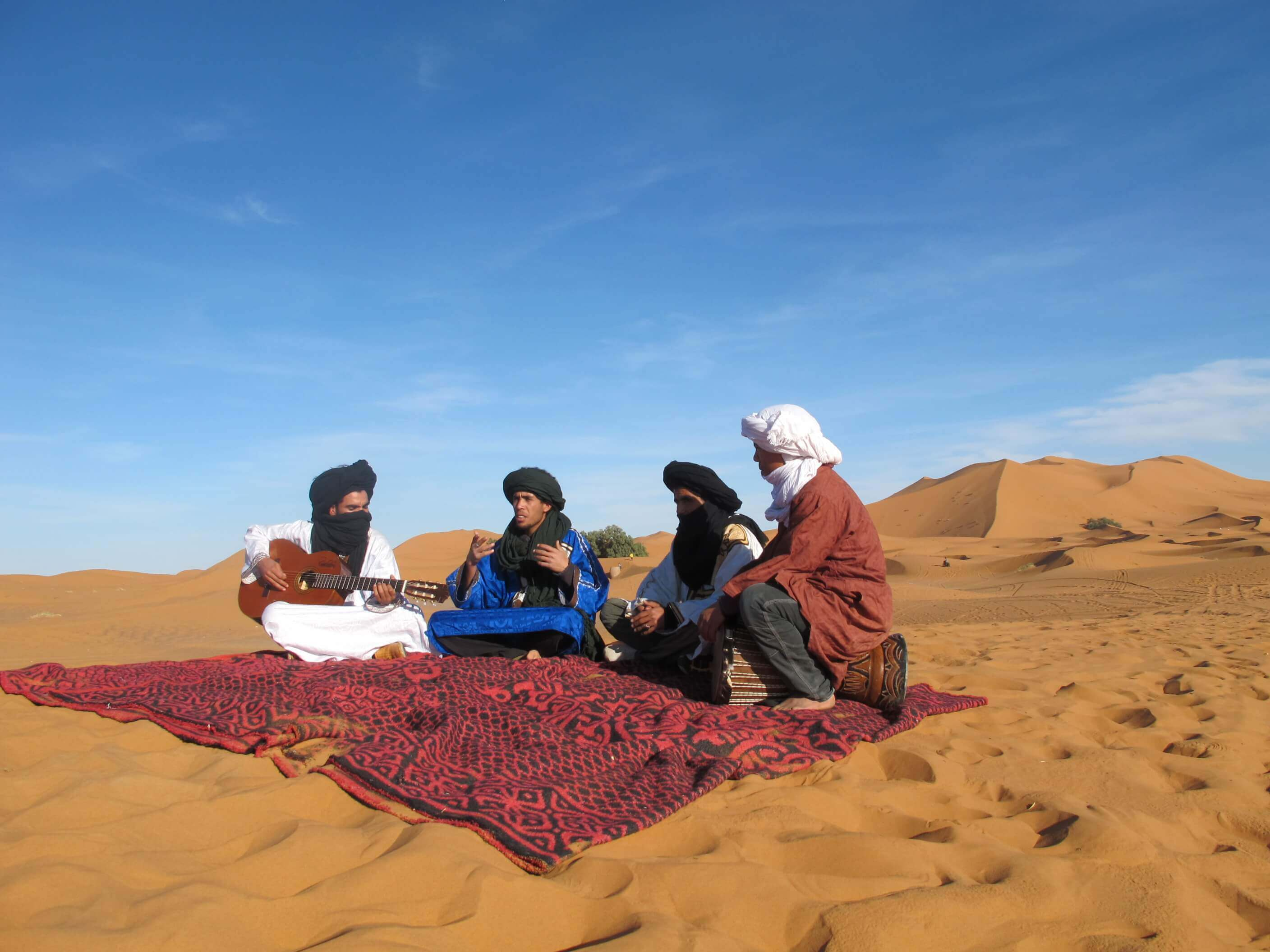 people playing instruments in the moroccan desert