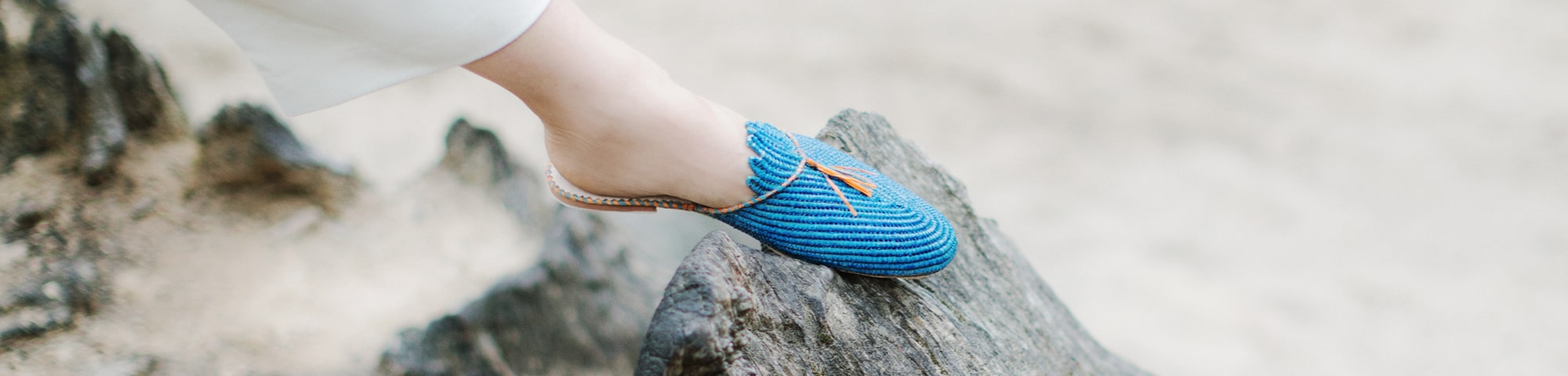 one foot wearing blue pompom raffia slippers by ABURY