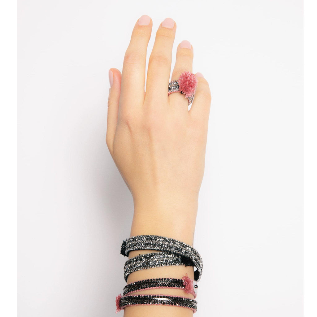 hand model wearing Rosé Woven Strass Ring with Pom Pom and bracelet